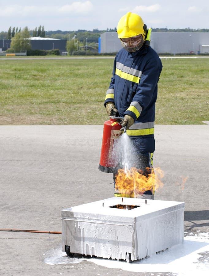 Firefighter using extinguisher stock photos