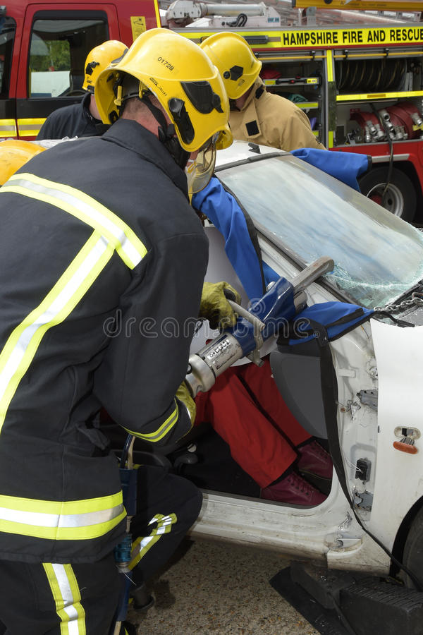 Firefighter using jaws of life at a car crash. Fire service officer cutting the roof from a crashed car using jaws of life Suitable for emergency service and stock images