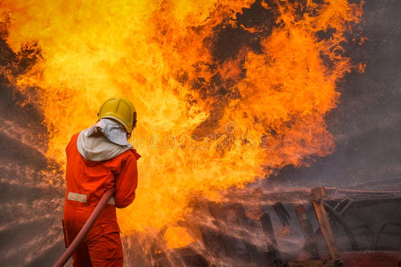Firefighter using water in fire fighting operation royalty free stock images