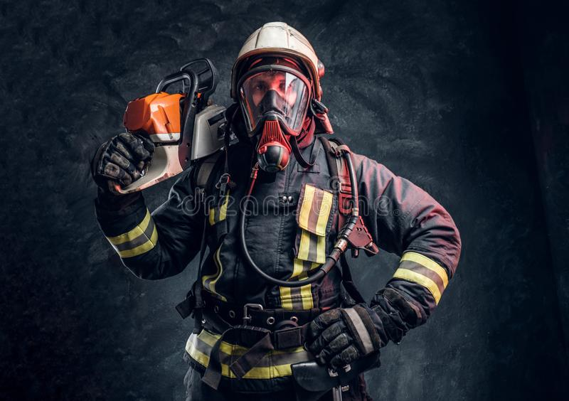 Firefighter wearing full protective equipment posing with a chainsaw on his shoulder. Studio photo against a dark. A brave firefighter wearing full protective stock images
