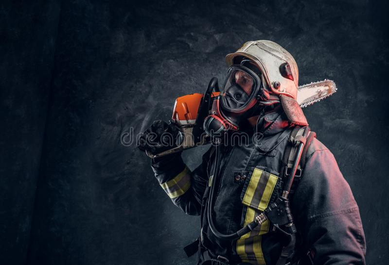 Firefighter wearing full protective equipment posing with a chainsaw on his shoulder. Studio photo against a dark. A brave firefighter wearing full protective stock photo