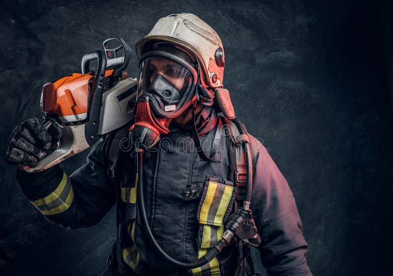 Firefighter wearing full protective equipment posing with a chainsaw on his shoulder. Studio photo against a dark. A brave firefighter wearing full protective royalty free stock images