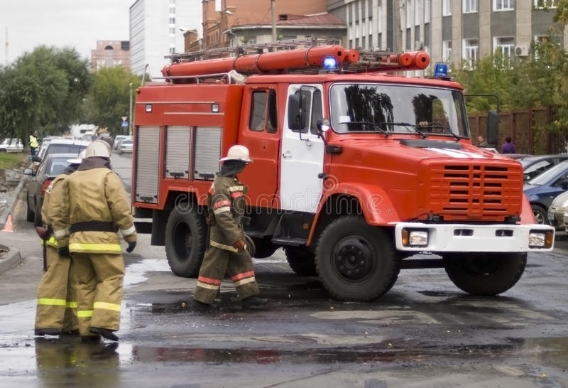 Firefighters. Three russian firefighters near the fire department car royalty free stock images