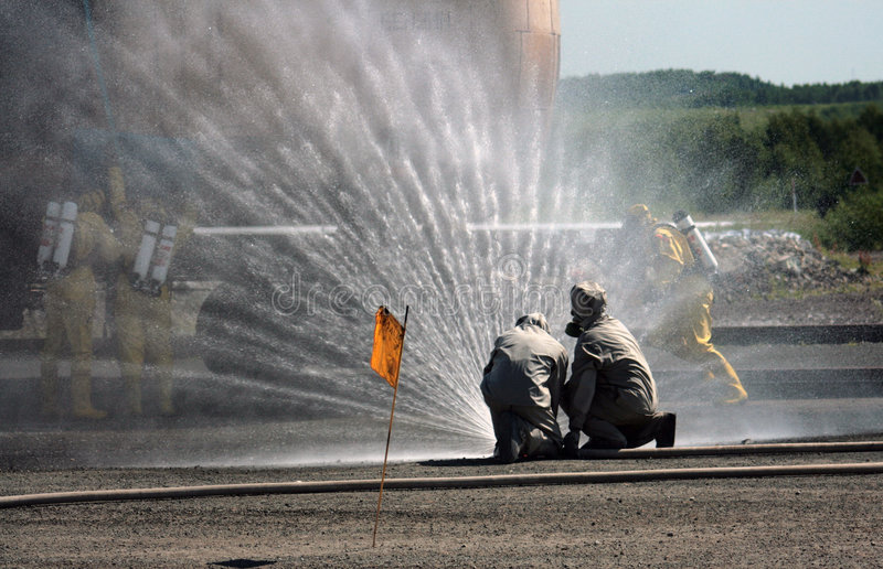 Firefighters. Firemen creating a jet of water during an emergency fire and rescue incident royalty free stock photo