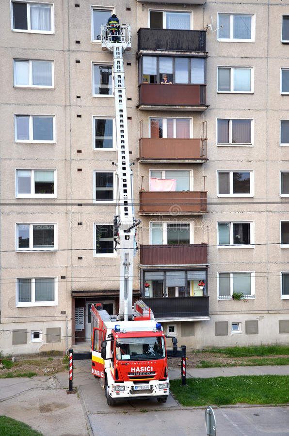Firefighters in action, a man uprise in telescopic boom basket of fire truck. Block of flats in background. Bytca, Slovakia - June 4, 2016: Firefighters in stock images
