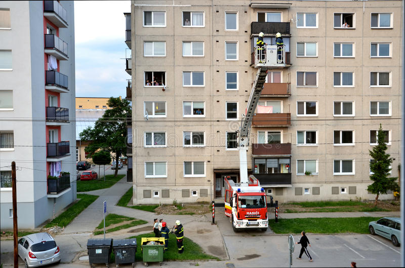 Firefighters in action, two men uprise in telescopic boom basket of fire truck. Some people are watching, block of flats in stock photo