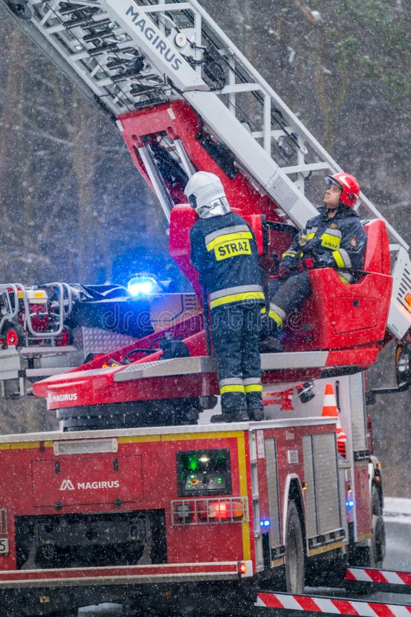 Firefighters cutting branches of a tree. Firefighters on the extendable crane are cutting branches of a tree for safety reasons after heavy snowfall in Karpacz stock photography