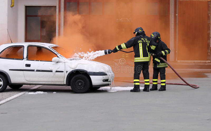 Firefighters during exercise to extinguish a fire in a car. Firemen during exercise to extinguish a fire in a car with foam royalty free stock image