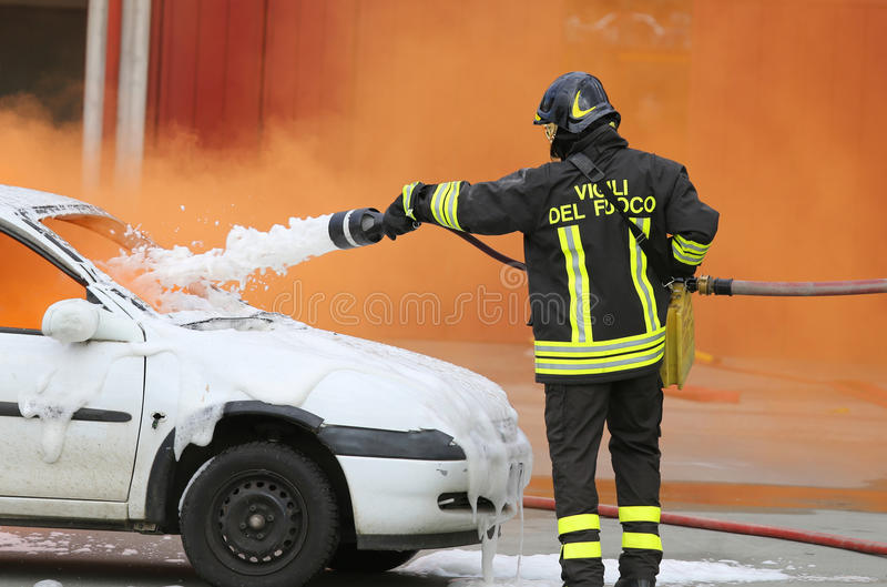Firefighters during exercise to extinguish a fire in a car. Firemen during exercise to extinguish a fire in a car with foam royalty free stock images