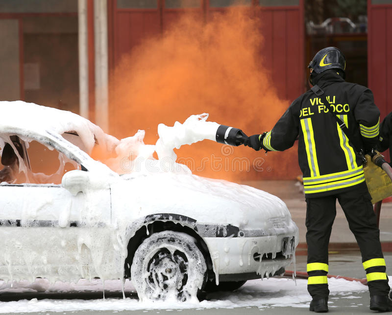 Firefighters during exercise to extinguish a fire in a car. Firemen during exercise to extinguish a fire in a car with foam stock image