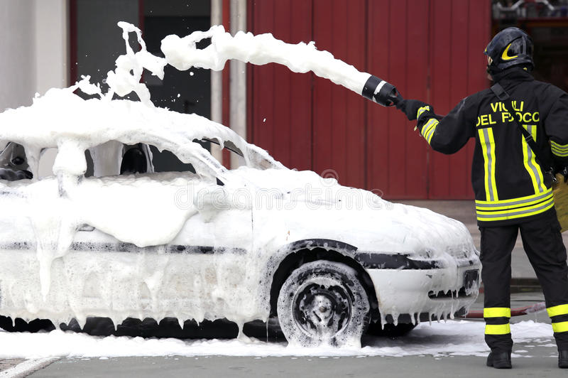 Firefighters during exercise to extinguish a fire in a car. Firemen during exercise to extinguish a fire in a car with foam stock photo