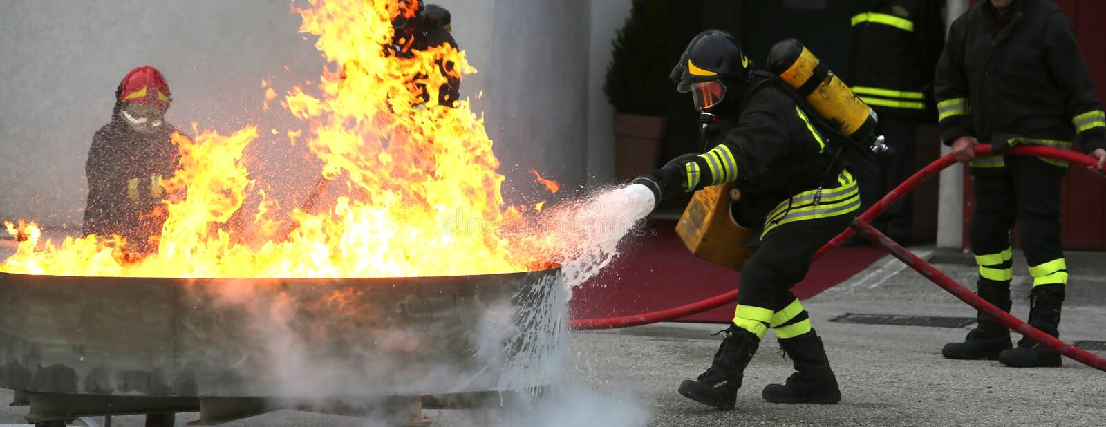 Firefighters during the exercise to extinguish a fire with foam royalty free stock photography
