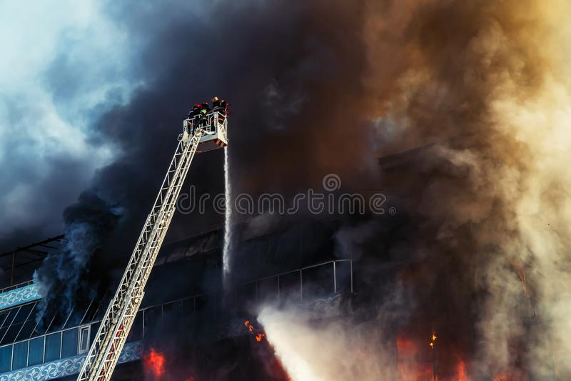 Firefighters extinguish a big fire. Black acrid smoke stock photos