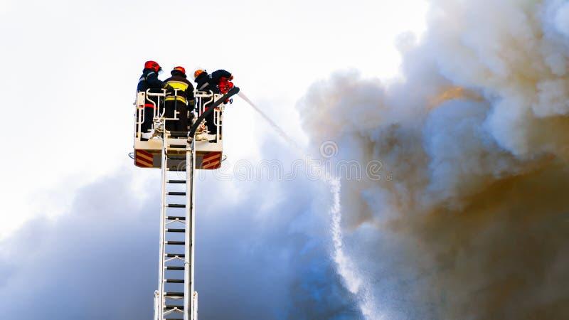 Firefighters extinguish a big fire. Black acrid smoke royalty free stock photo
