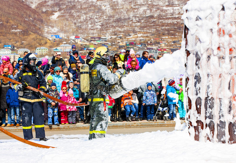 Firefighters extinguish the fire with foam in the smoke. Kamchatka, Russia - 30 April, 2017: Feast in Petropavlovsk-Kamchatsky. Birthday fire service in Russia royalty free stock photos