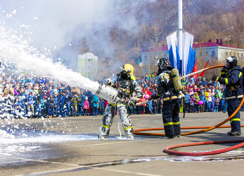 Firefighters extinguish the fire with foam in the smoke. Kamchatka, Russia - 30 April, 2017: Feast in Petropavlovsk-Kamchatsky. Birthday fire service in Russia stock image