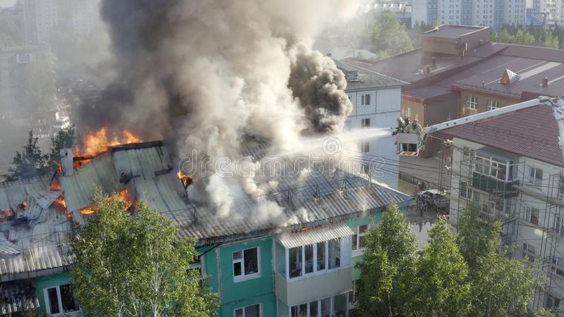 Firefighters extinguish a fire on the roof of a residential highrise building. top view stock photos
