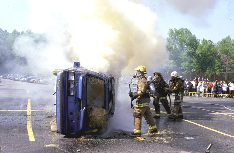 Firefighters fighting a car fire where a car i s flipped overs royalty free stock photo