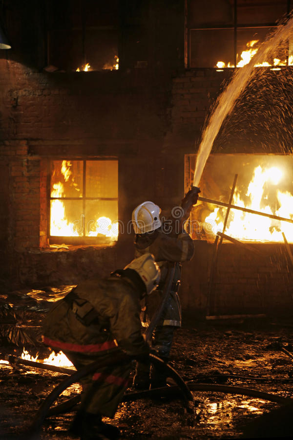 Firefighters fighting a fire stock images