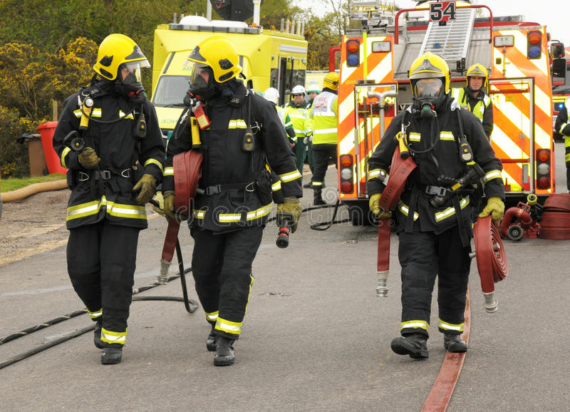 Firefighters and hoses. Hampshire, England. May 2012. Firefighters in breathing apparatus walk out their hoses at the scene of an incident stock photo