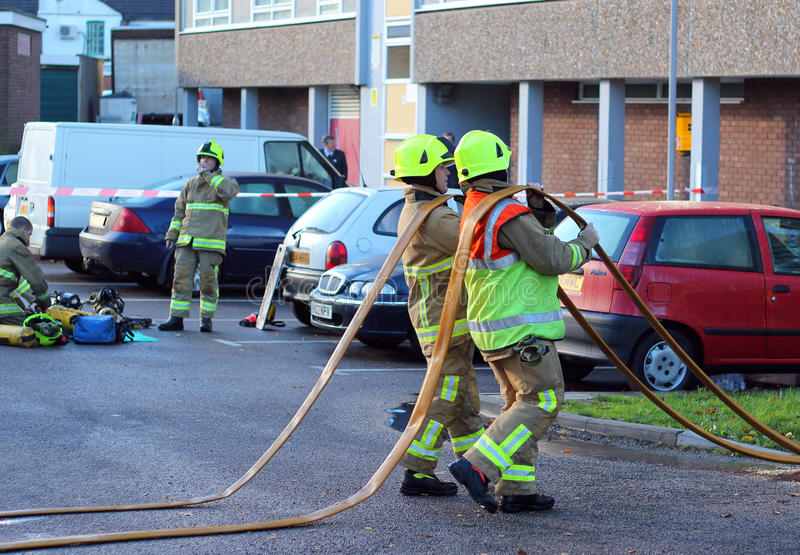 Firefighters with hoses. Firemen draining water from their hoses after attending a fire in Bedford, UK on Friday 23rd November, 2012. A small fire in a large stock photos