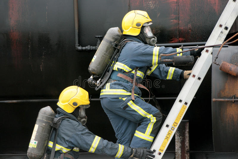 Firefighters on ladder. Fire-fighter in full BA on ladder stock photography