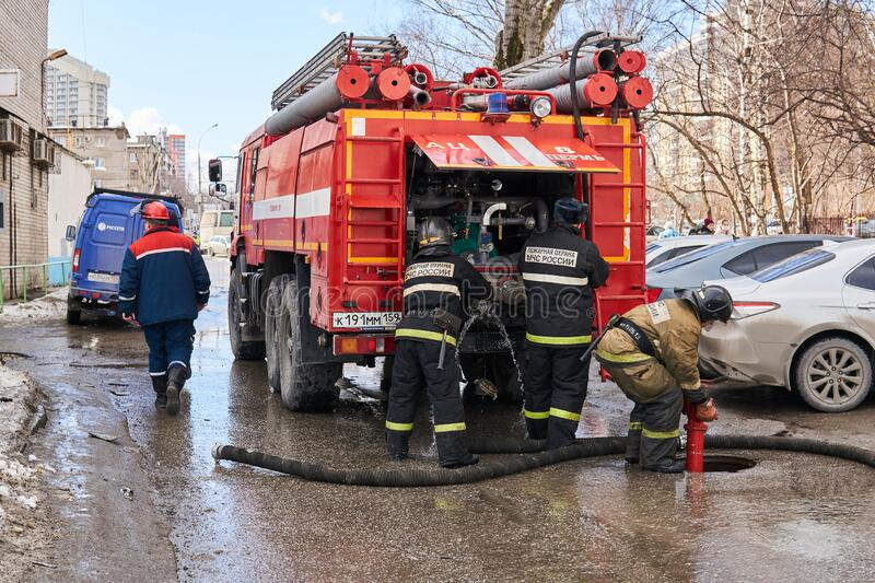 Firefighters of the Ministry for Emergency Situations of the Russian Federation use a fire hydrant next to the fire truck. Perm, Russia - March 20, 2020 stock photo