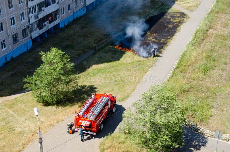 Firefighters near the fire truck are preparing to extinguish a burning lawn with grass in the city royalty free stock photos