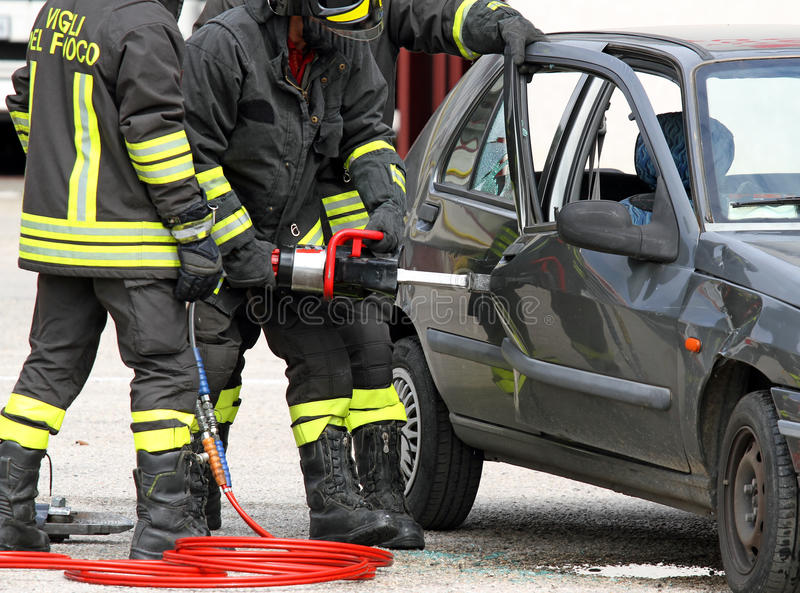 Firefighters open the door with a powerful pneumatic shears. Firefighters open the door of the car with a powerful pneumatic shears stock images