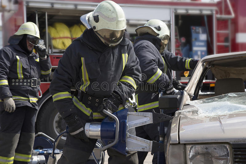 Firefighters with the pneumatic shears open the car doors. After a car accident royalty free stock photo
