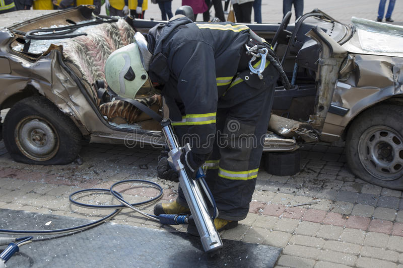 Firefighters with the pneumatic shears open the car doors. After a car accident royalty free stock image