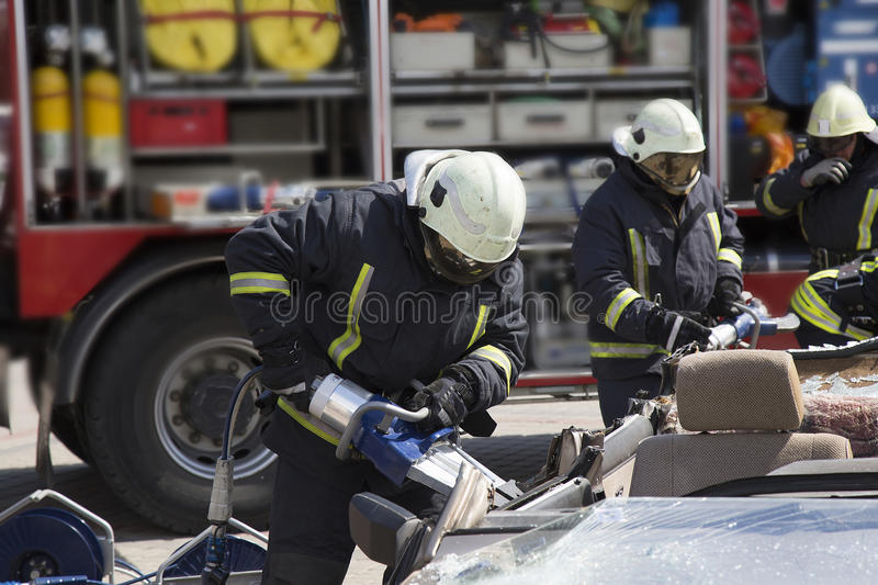 Firefighters with the pneumatic shears open the car doors. After a car accident stock photos