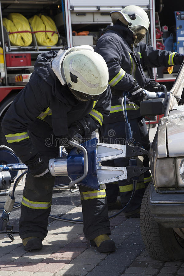 Firefighters with the pneumatic shears open the car doors. After a car accident royalty free stock photos