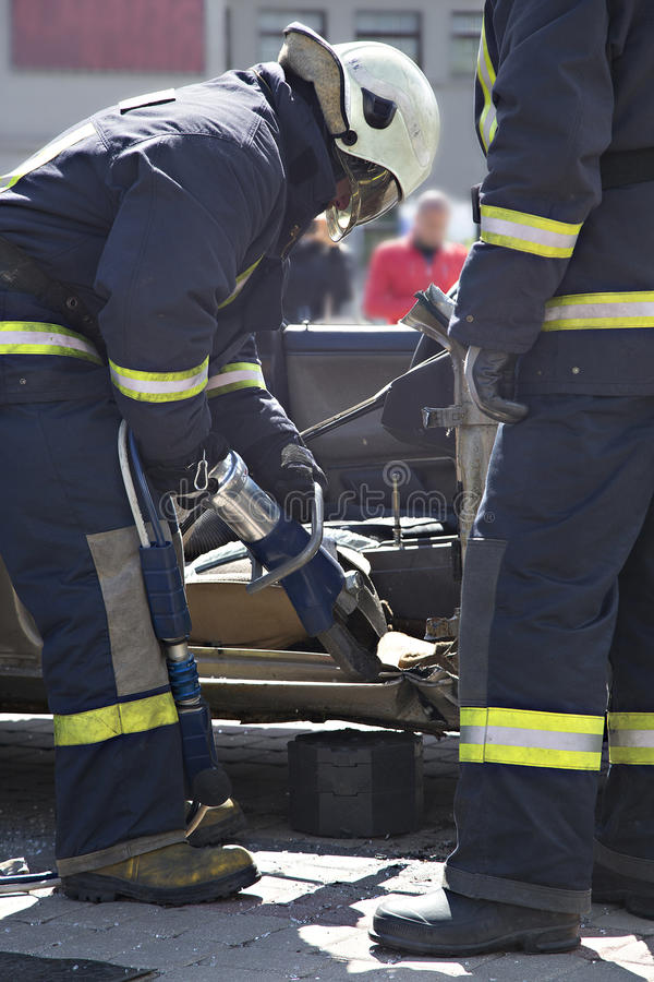 Firefighters with the pneumatic shears open the car doors. After a car accident royalty free stock images