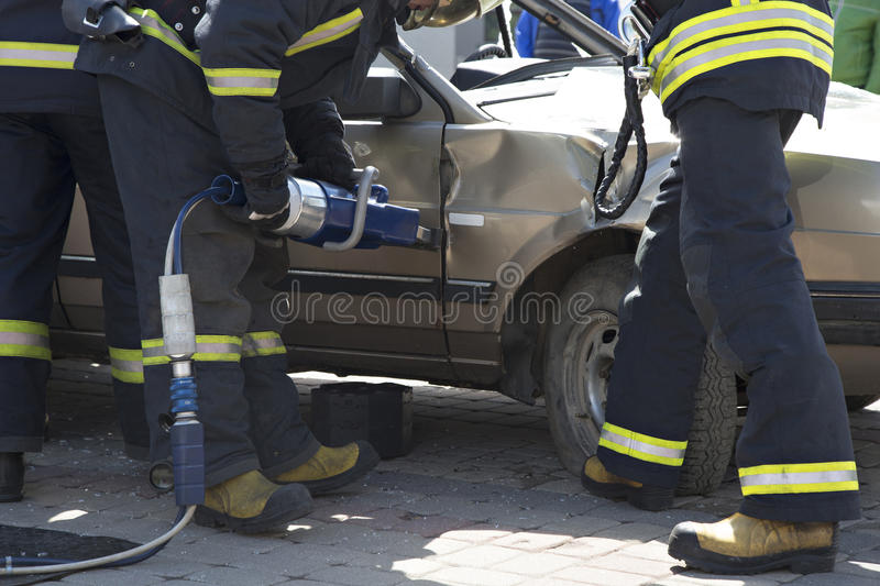 Firefighters with the pneumatic shears open the car doors. After a car accident stock photo