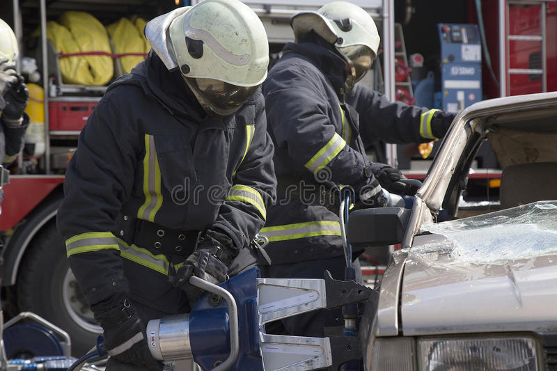 Firefighters with the pneumatic shears open the car doors. After a car accident stock images