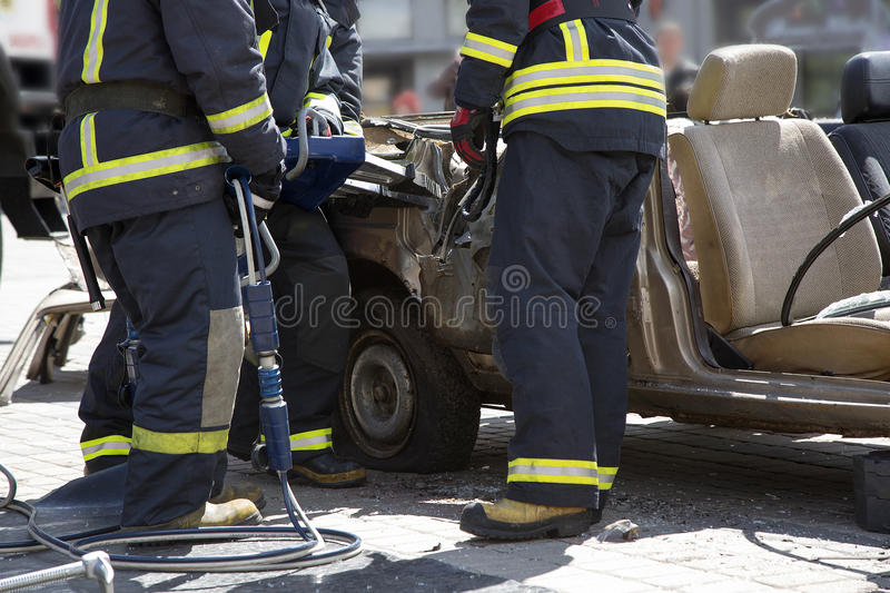 Firefighters with the pneumatic shears open the car doors. After a car accident stock image