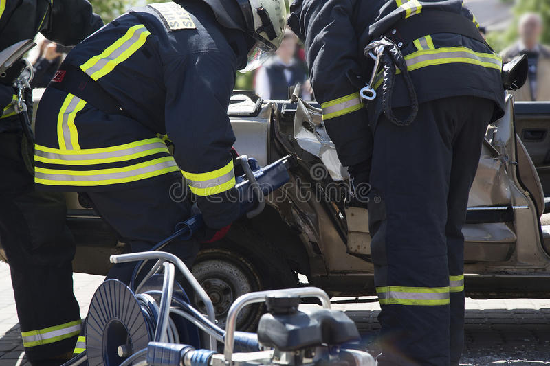 Firefighters with the pneumatic shears open the car doors. After a car accident royalty free stock photography
