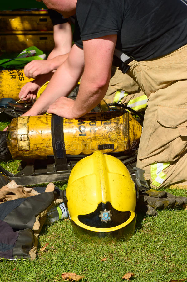 Firefighters prepare breathing apparatus at fire scene. Firefighters prepare breathing apparatus at the scene of a fire stock images
