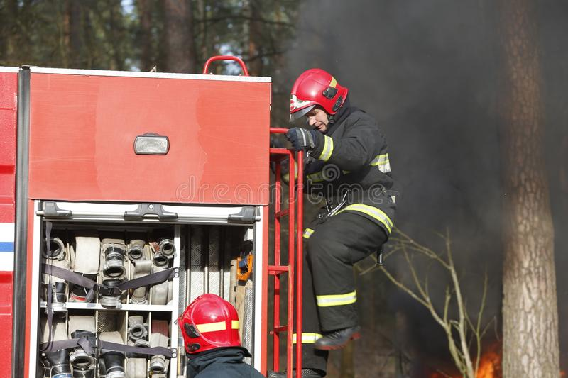 Firefighters preparing to extinguish a fire stock image