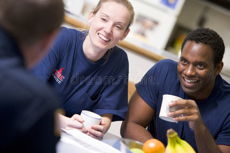 Firefighters relaxing in the staff kitchen royalty free stock images