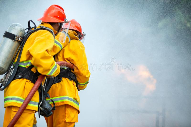 Firefighters spraying high pressure water to fire with copy space, Big bonfire in training, Firefighter wearing a fire suit for stock photography