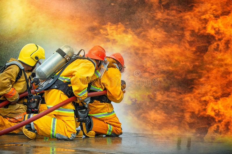 Firefighters spraying high pressure water to fire with copy space, Big bonfire in training, Firefighter wearing a fire suit for. Safety under the danger case stock photography