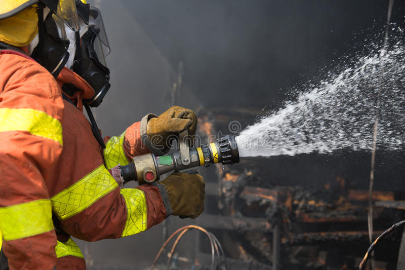 2 firefighters spraying water in fire fighting operation. Close up 2 firefighters budddy spraying water in fire fighting operation stock image