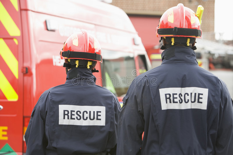 Firefighters standing by a small fire engine royalty free stock photo