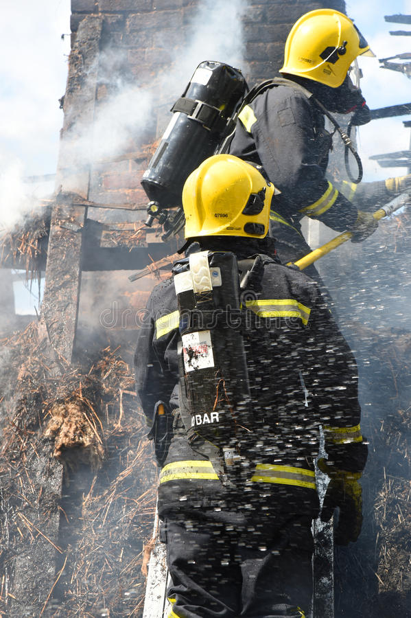 Firefighters tackle a fire on a cottage roof. Firefighters tackle a fire in an historic thatch roof cottage amid smoke and blue sky royalty free stock photos