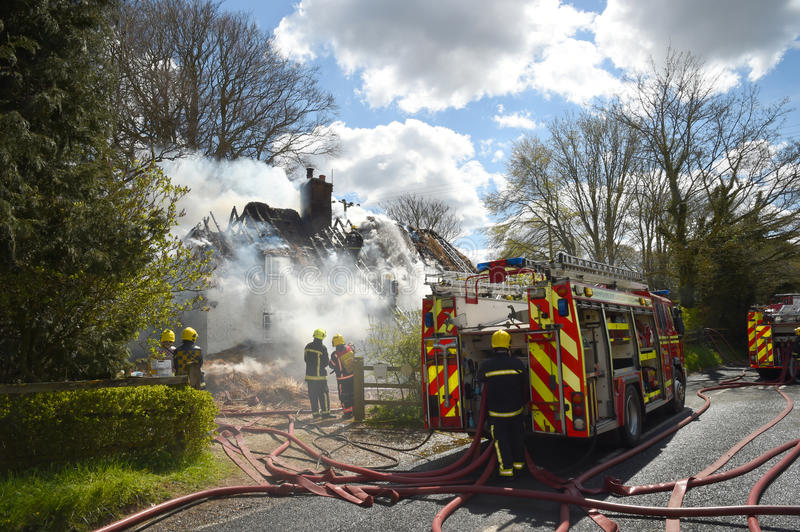 Firefighters tackle a fire in a rural cottage. Firefighters tackle a fire in an historic thatch roof cottage in a rural location stock photography