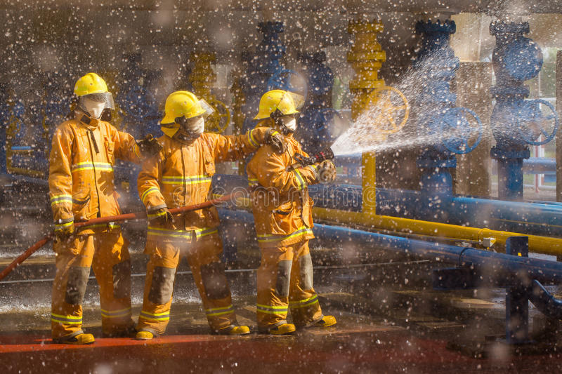 Firefighters training, foreground is drop of water drop Spr stock images
