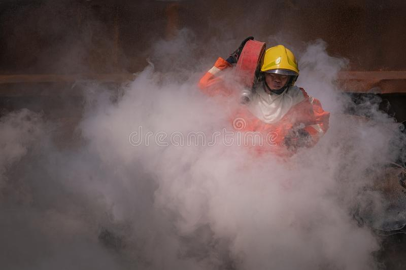 Firefighters training Team practice to fighting with fire in emergency situation. A fireman carry a water hose run through flame stock photos