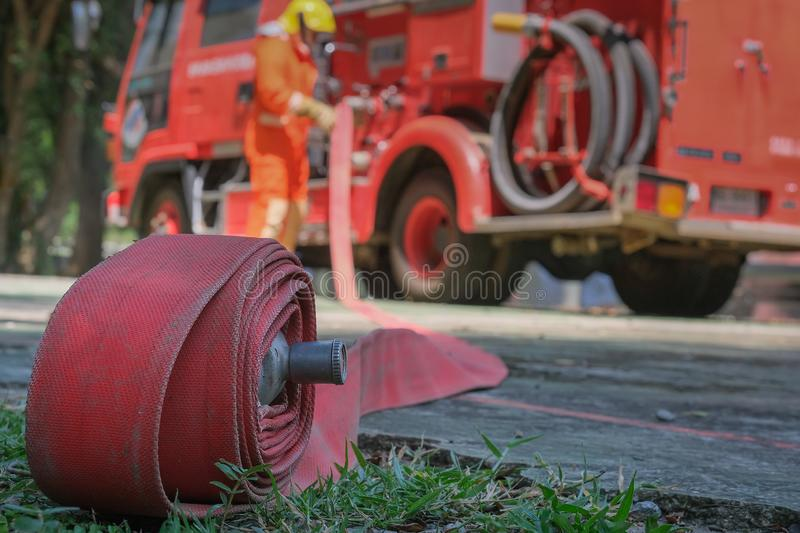 Firefighters training Team practice to fighting with fire in emergency situation. A fireman carry a water hose run through flame royalty free stock images